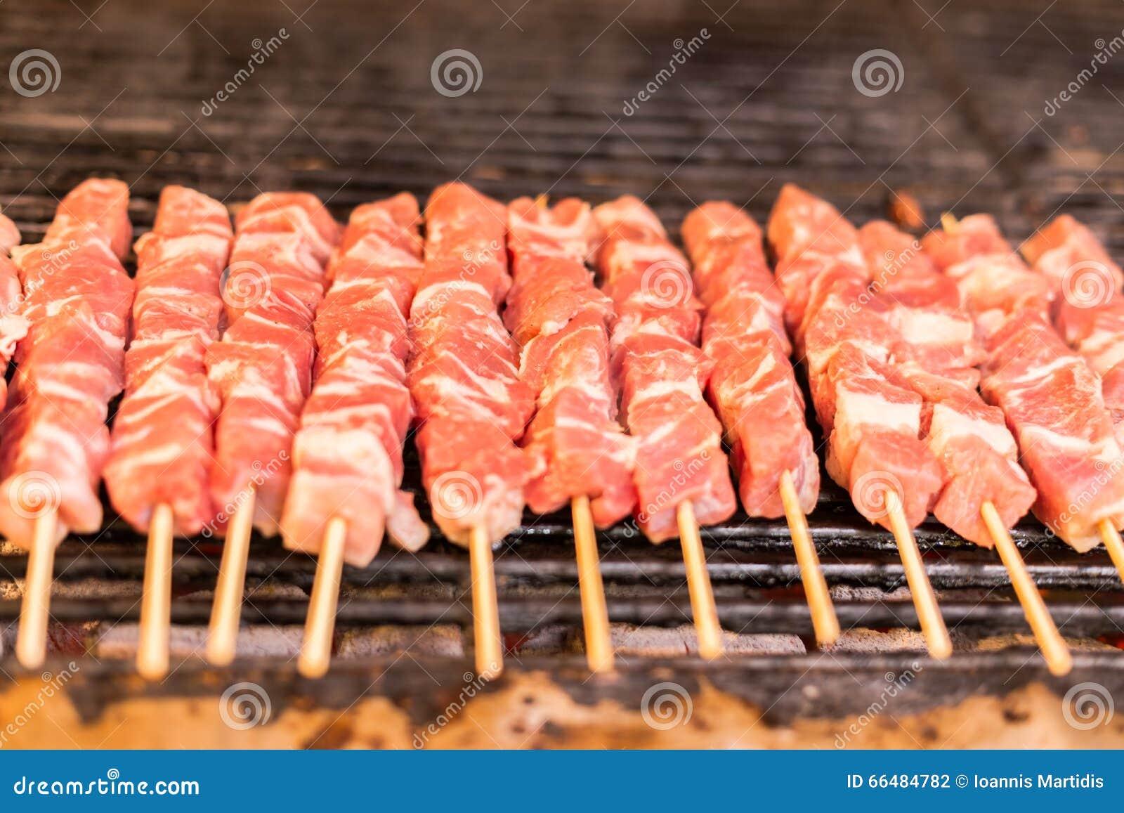 Los prendederos crudos frescos del pecho del cerdo de la carne roja en una rejilla de la parrilla de la barbacoa del pincho asan