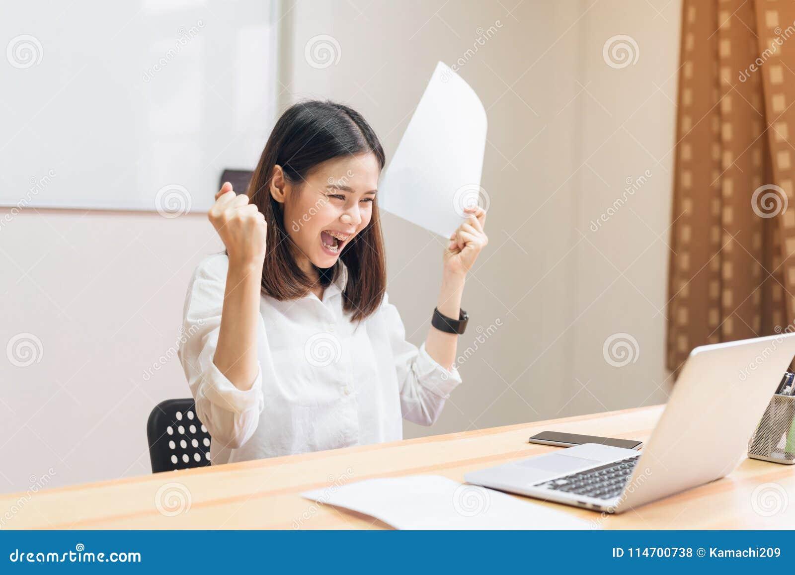 Los puños de las mujeres de negocios que eran emocionados de éxito expresaron alegría porque trabajan para alcanzar sus metas