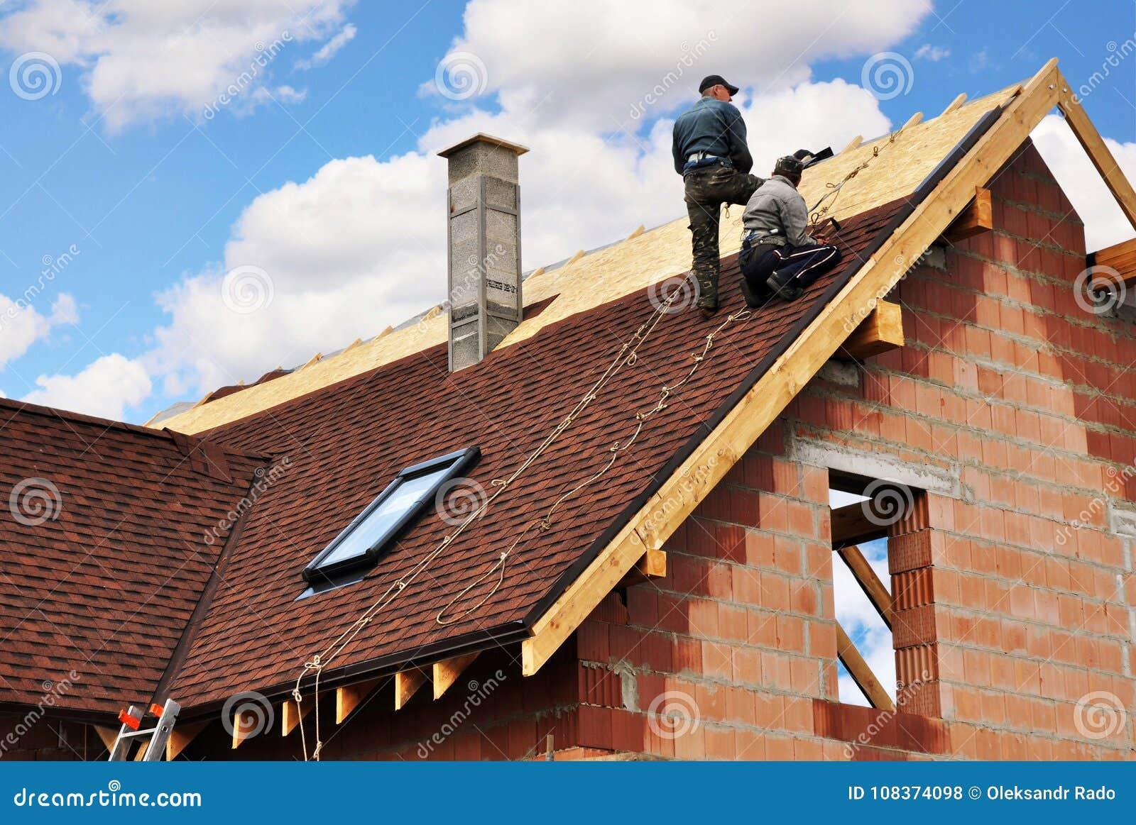 Los Roofers ponen e instalan tablas del asfalto Reparación del tejado con dos roofers Construcción de la techumbre con las tejas