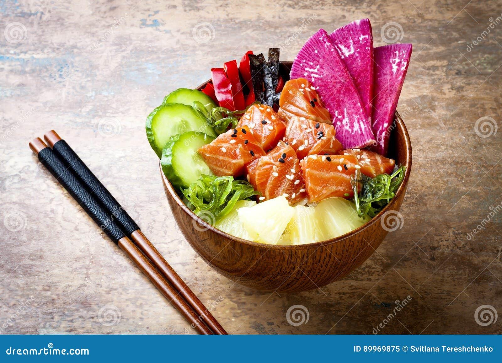 Los salmones hawaianos empujan el cuenco con las semillas de la alga marina, del rábano de la sandía, del pepino, de la piña y de