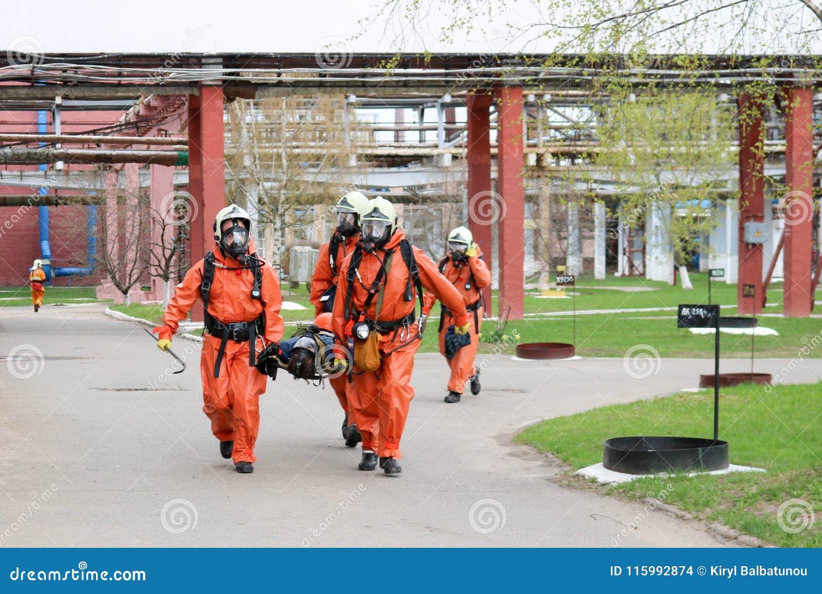 Los salvadores profesionales de los bomberos en trajes resistentes al fuego protectores anaranjados, cascos blancos y caretas ant