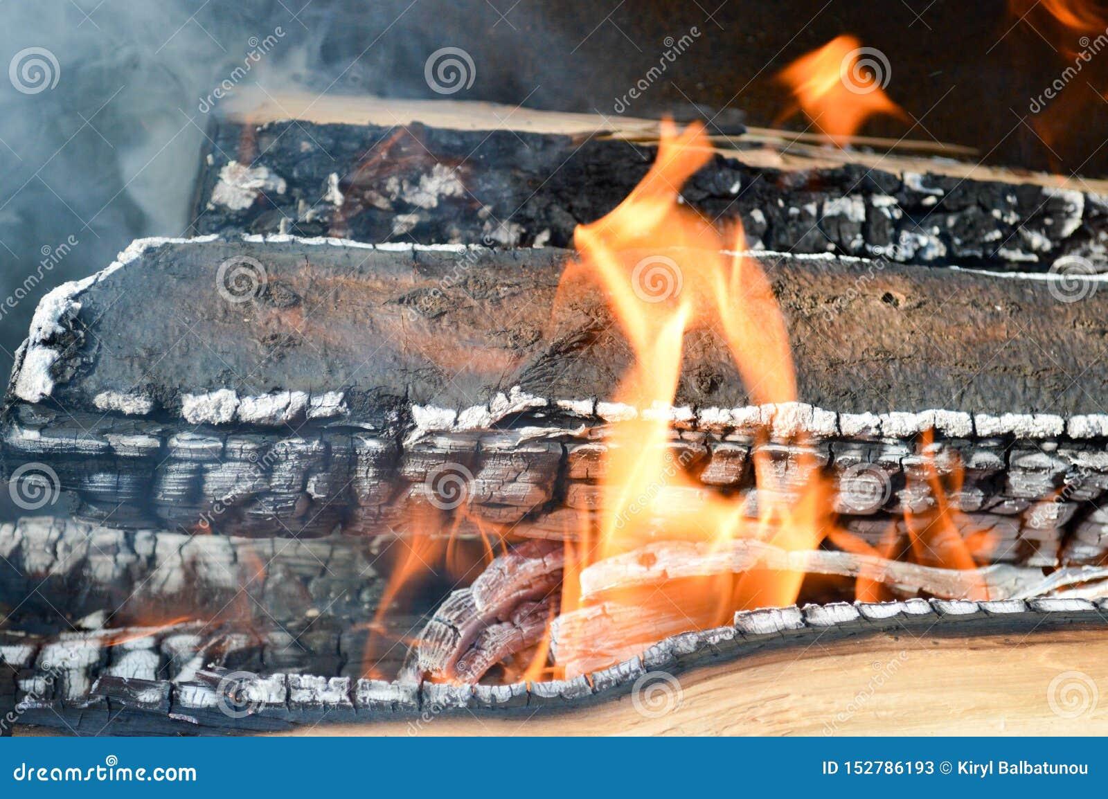 Los tablones carbonizados calientes ardientes de madera de la madera abren una sesión un fuego con las lenguas del fuego y del hu