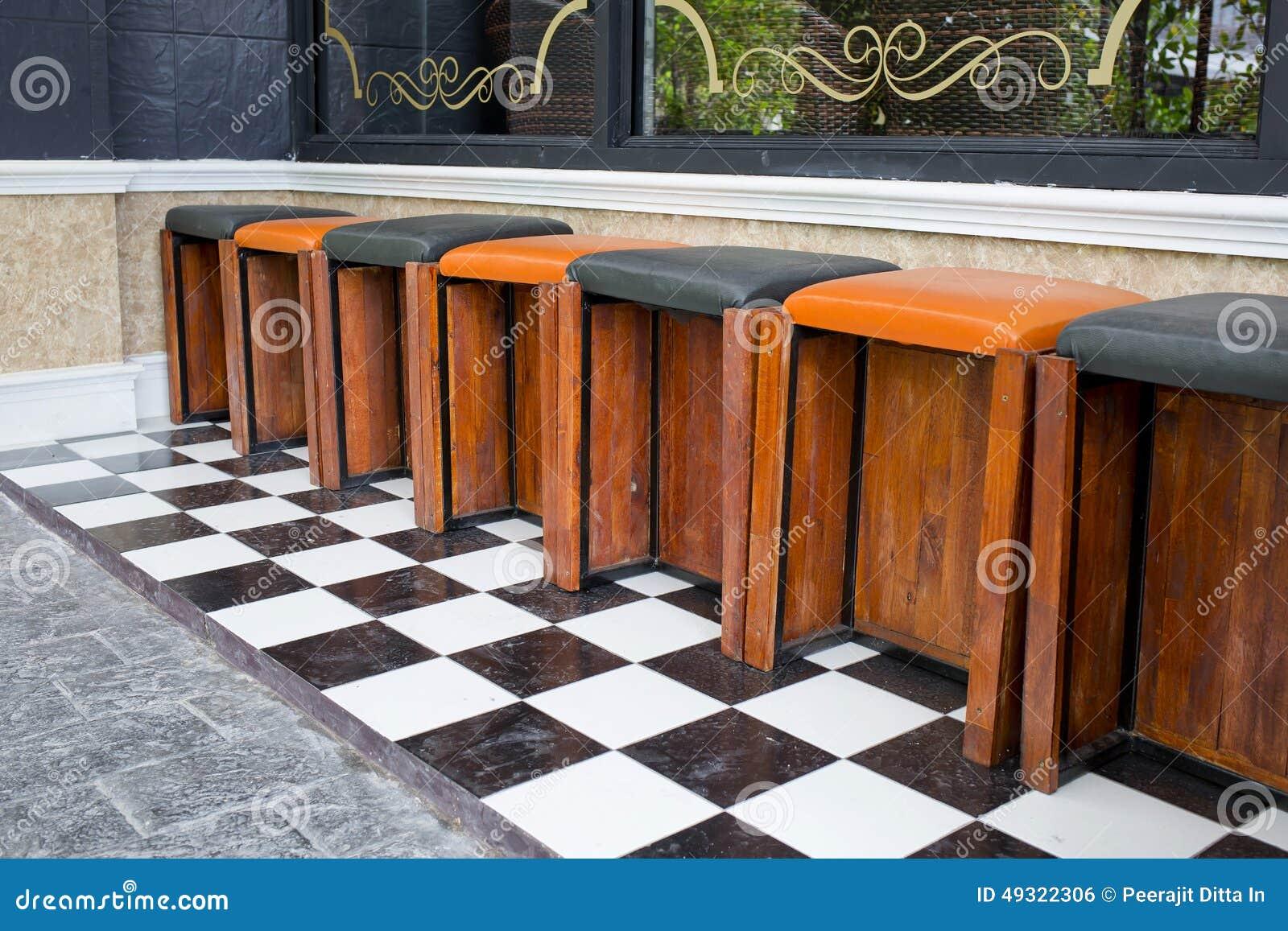 Los taburetes de bar de madera cl sicos se alinean en una for Fotos de bares de madera