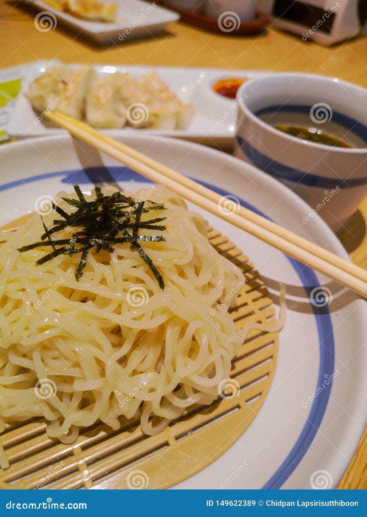 Los tallarines fr?os vertieron con alga marina secada en un sistema de platos japoneses