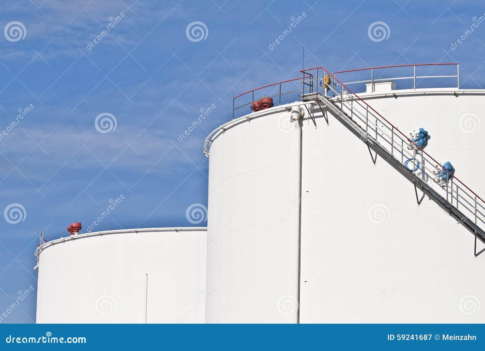 Los tanques blancos en granja del tanque con el cielo azul