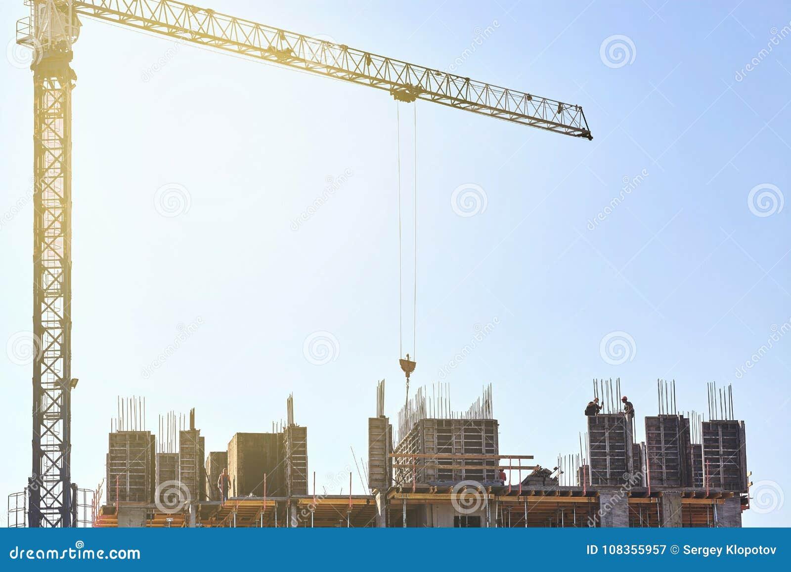 Los trabajadores de los constructores instalan una placa para el hormigón de colada con un hig