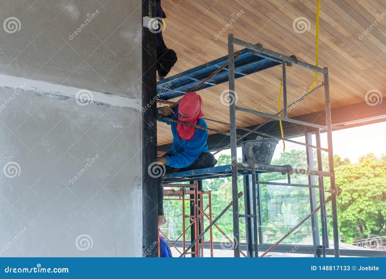 Los trabajadores de sexo femenino asiáticos que llevan las camisetas de manga larga azules y los sombreros rojos son andamio para