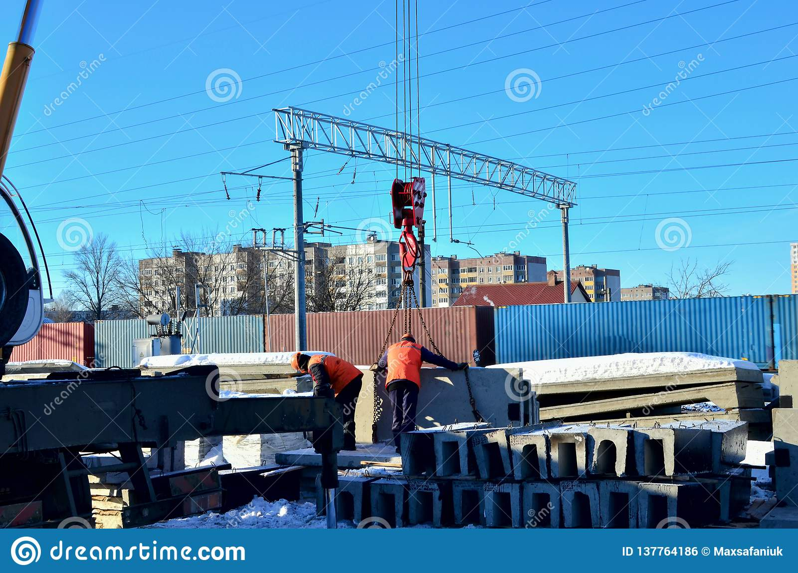 Los trabajadores están ayudando a la grúa móvil para manejar la vigueta concreta