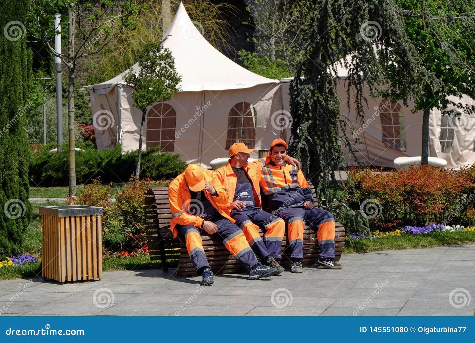 Los trabajadores municipales de la ciudad se están sentando en un banco para el breve descanso después de limpiar el día soleado