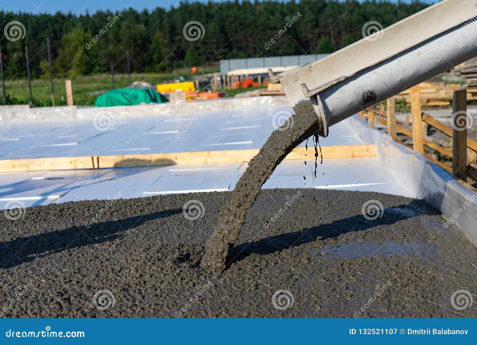 Los trabajadores vierten la fundación para la construcción de un edificio residencial usando los mezcladores concretos móviles