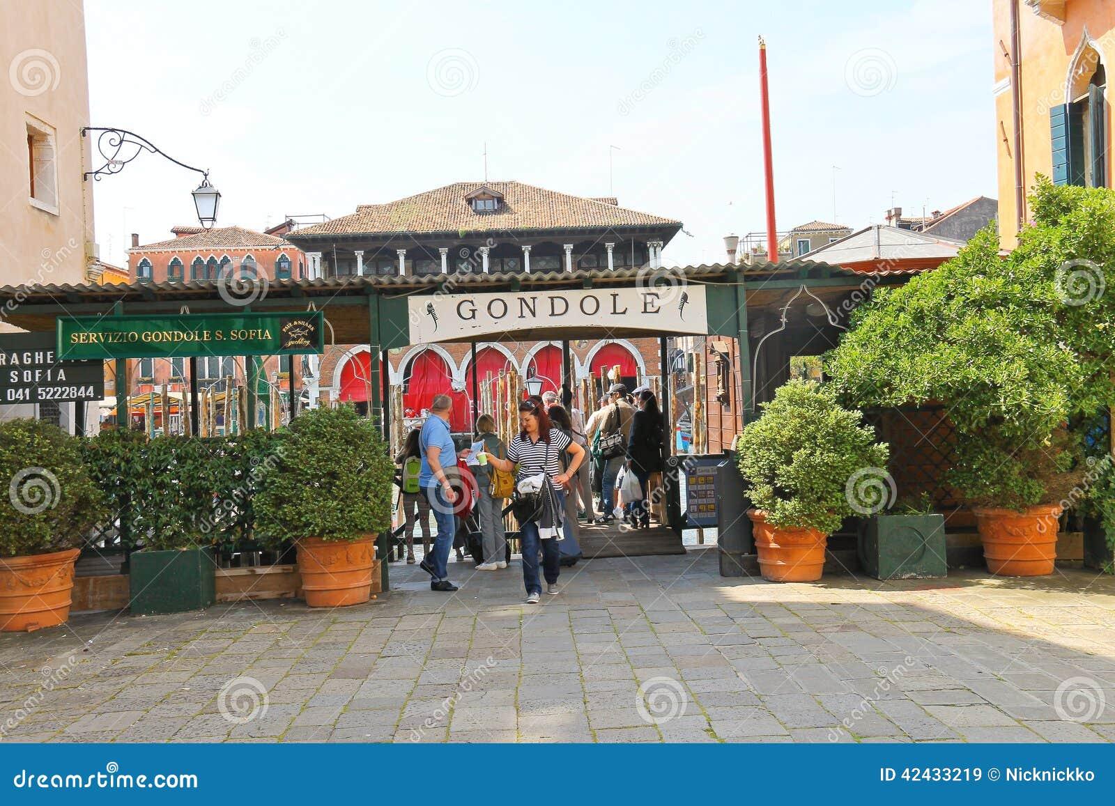 Los turistas acercan a servicio de la góndola en el canal en Venecia, Italia