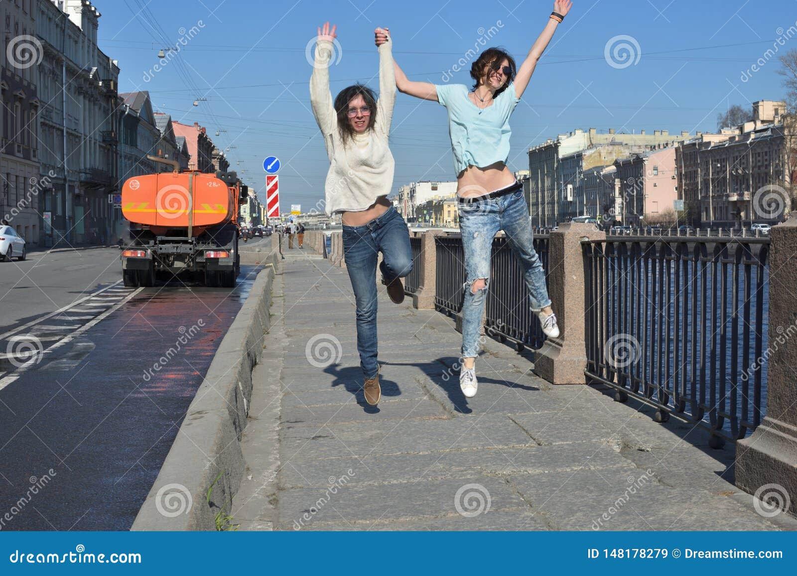 Los turistas de las se?oras jovenes en St Petersburg Rusia se divierten junto en un d?a soleado, un desvestido y un salto de la a