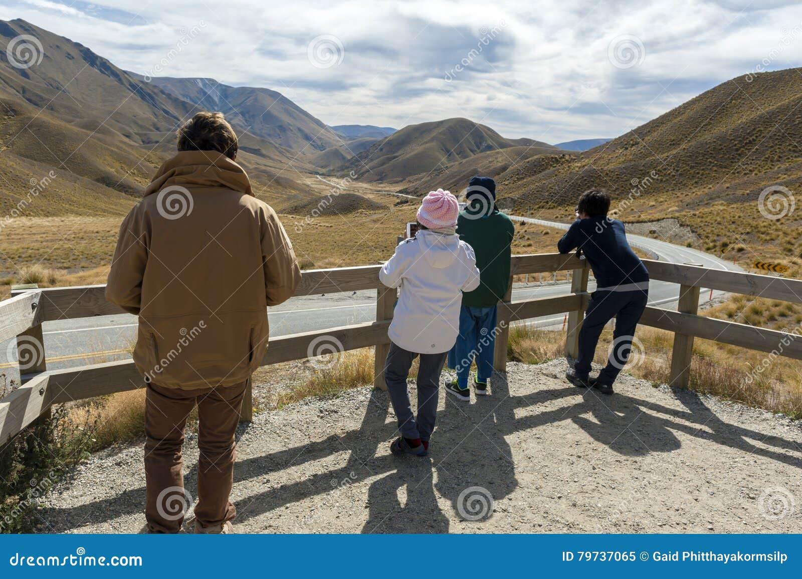 Los turistas en el puesto de observación escénico de Lindis pasan, Nueva Zelanda