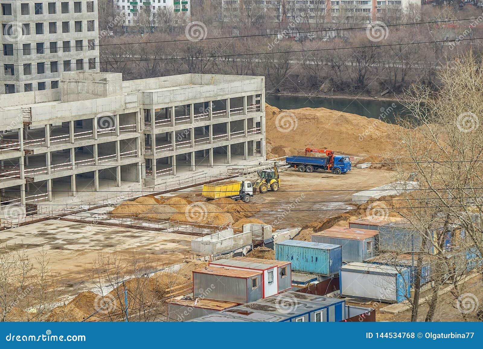 Los vehículos de la construcción están manejando el emplazamiento de la obra