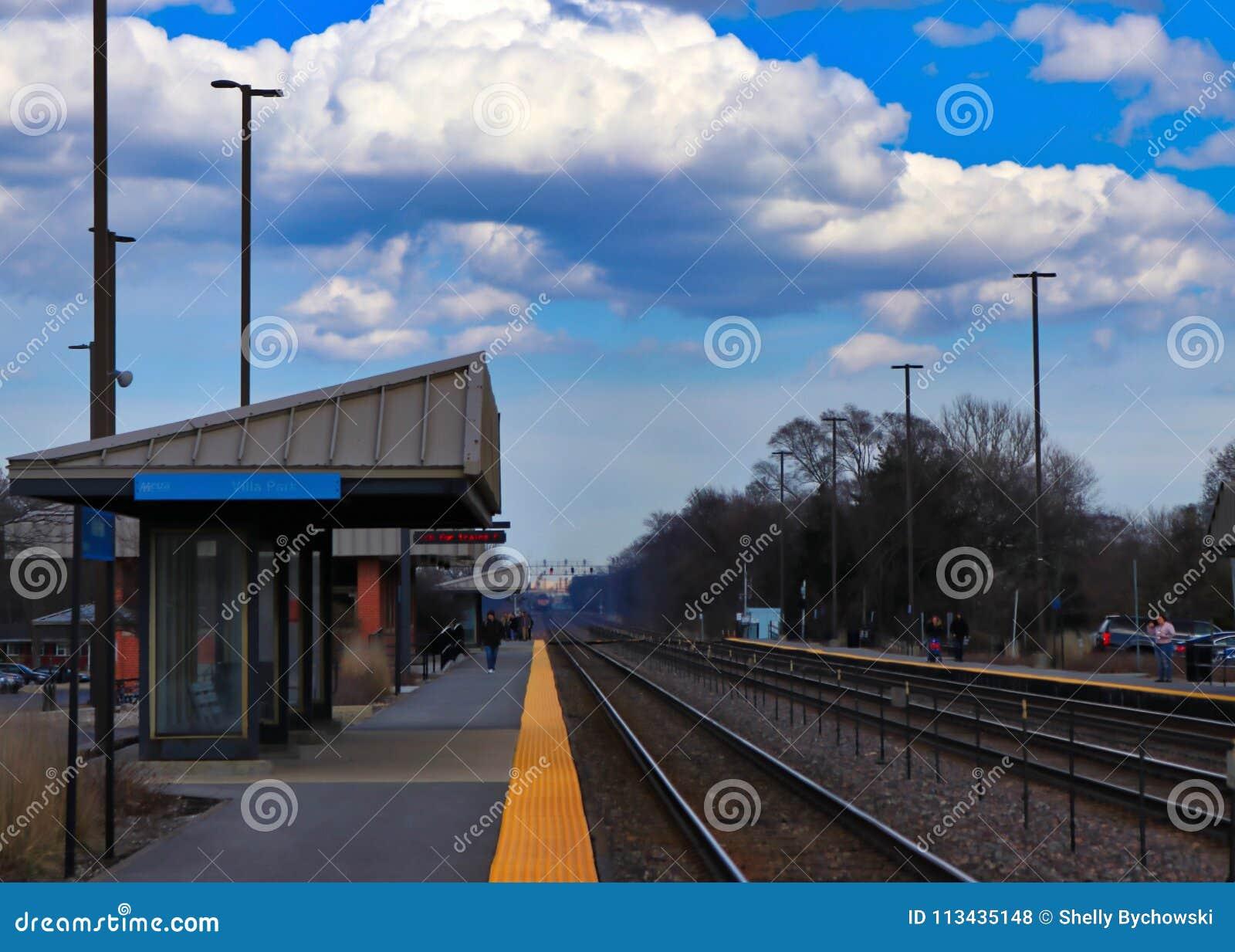 Los viajeros en la plataforma de la estación después del tren de Metra pasan a través de una estación de tren del ` s del suburbi