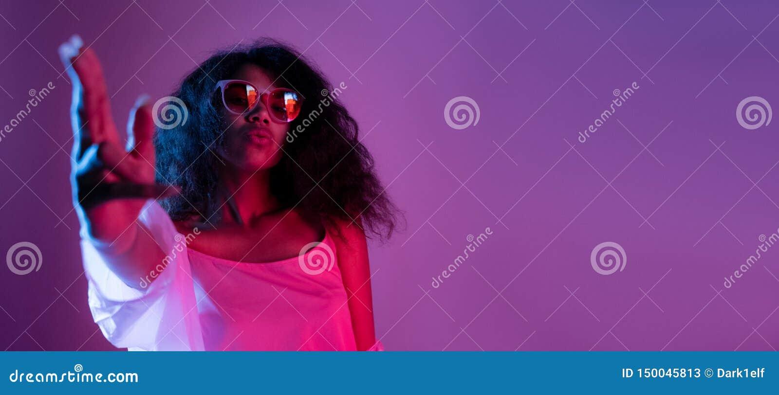 Los vidrios africanos del desgaste de la muchacha de la moda bailan en fondo púrpura del partido de disco