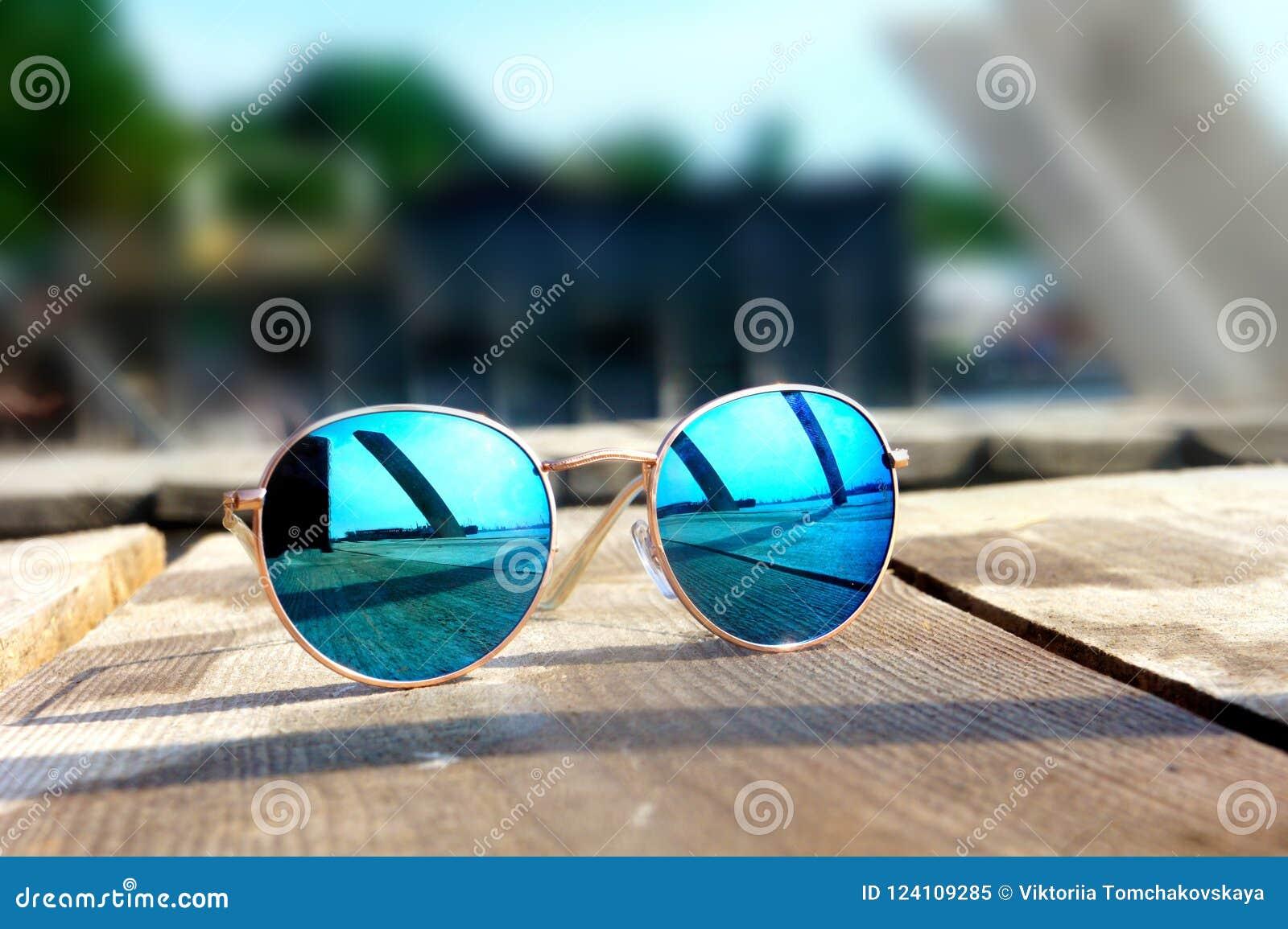 Los vidrios con los vidrios azules en el sol mienten en un resto de madera del piso