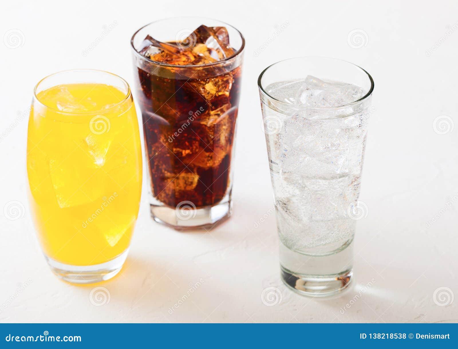 Los vidrios de soda beben con los cubos y las burbujas de hielo en el fondo de piedra de la tabla de cocina Cola y soda anaranjad