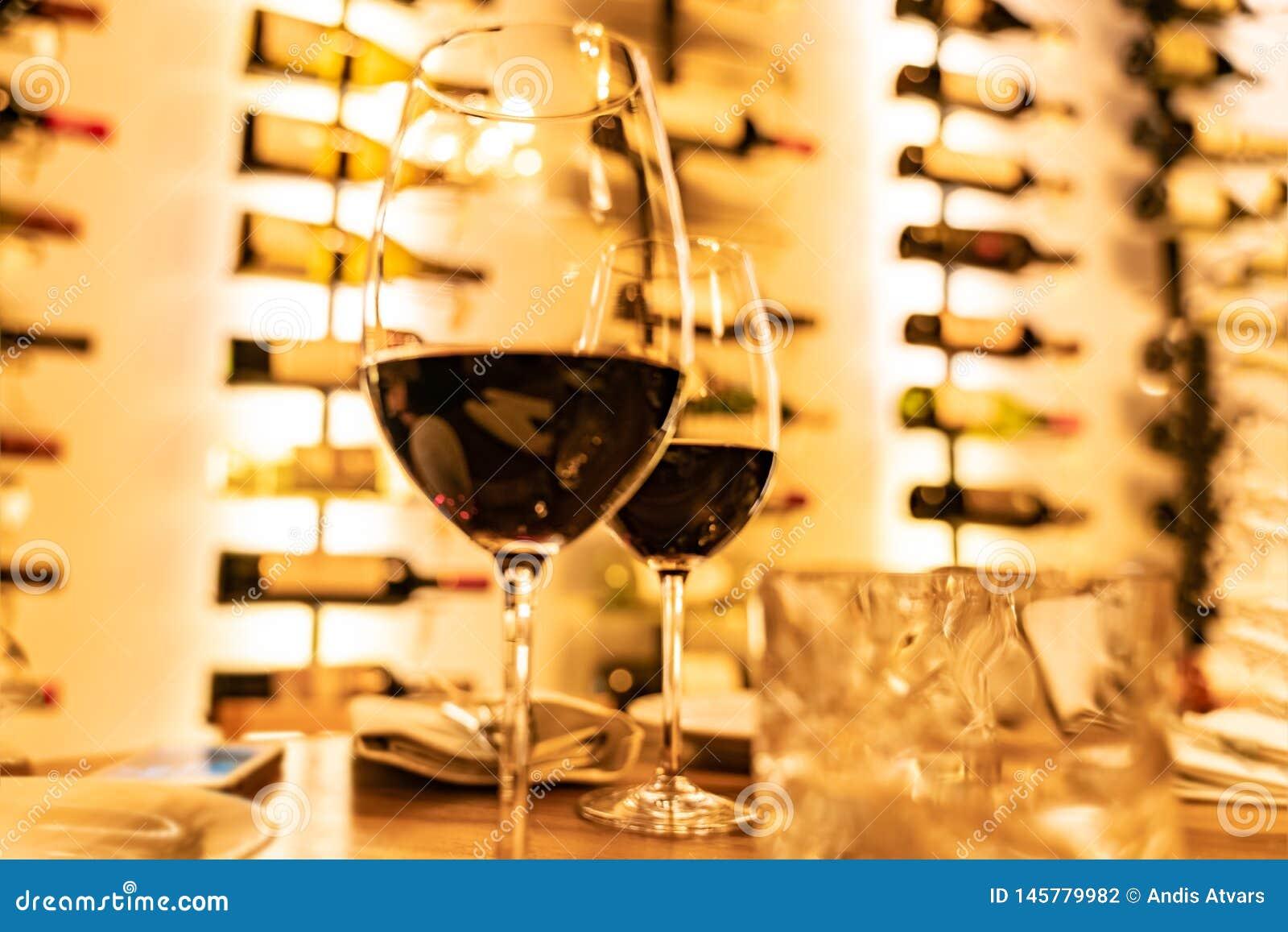Los vidrios de vino tinto en un tablón de madera con las botellas defocused atormentan en el fondo