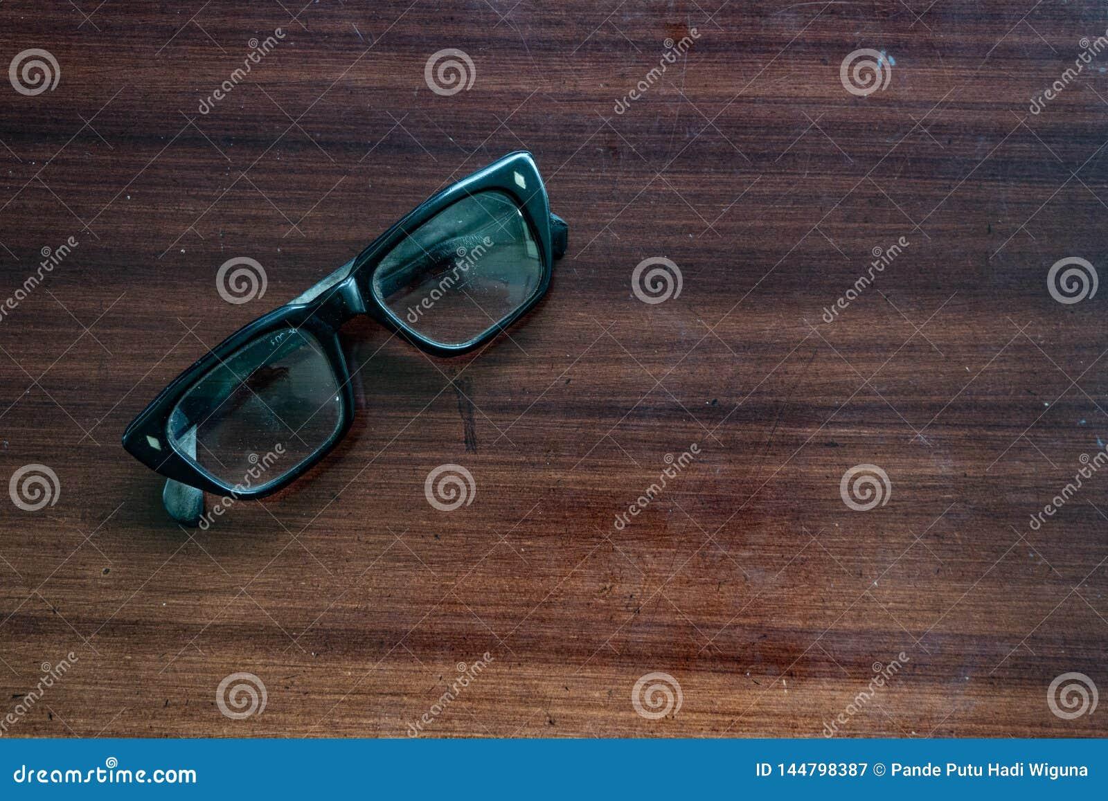 Los vidrios viejos en la tabla de madera marrón eran poco polvorientos