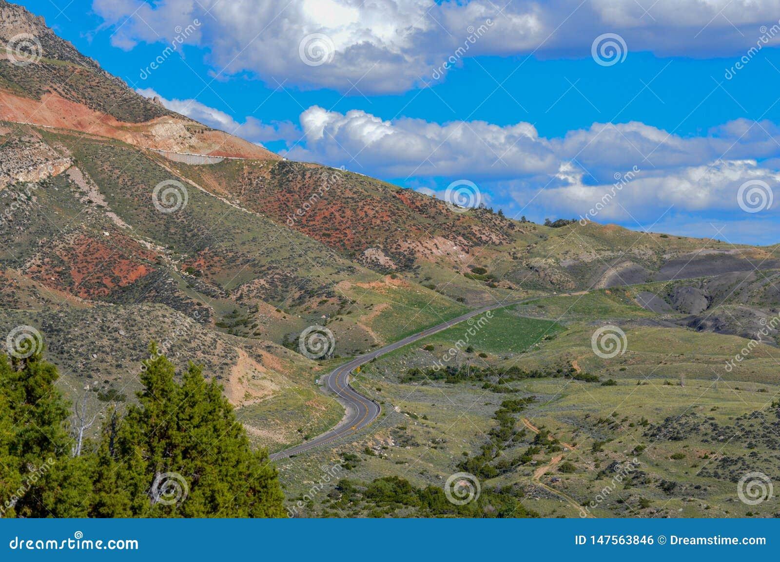 Los vientos del camino a lo largo de la base de la cordillera enorme en Wyoming septentrional