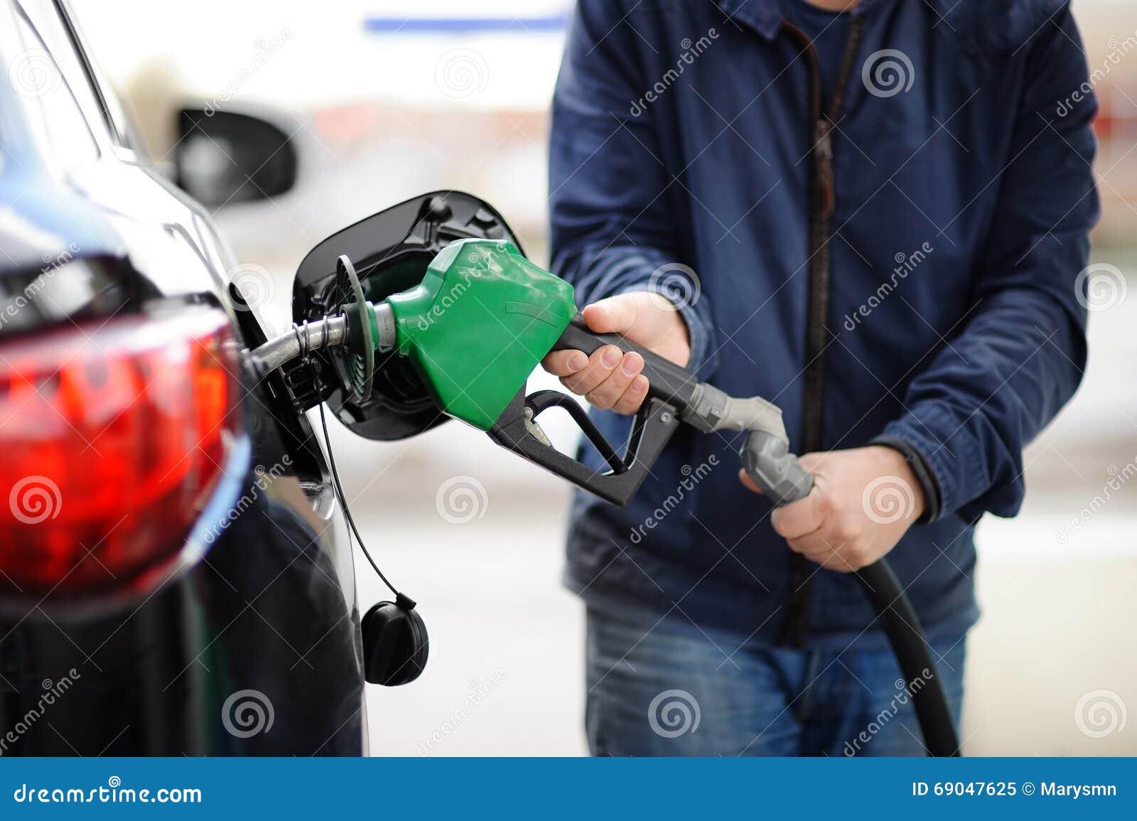 ? loseup van brandstof van de mensen de pompende benzine in auto bij benzinestation