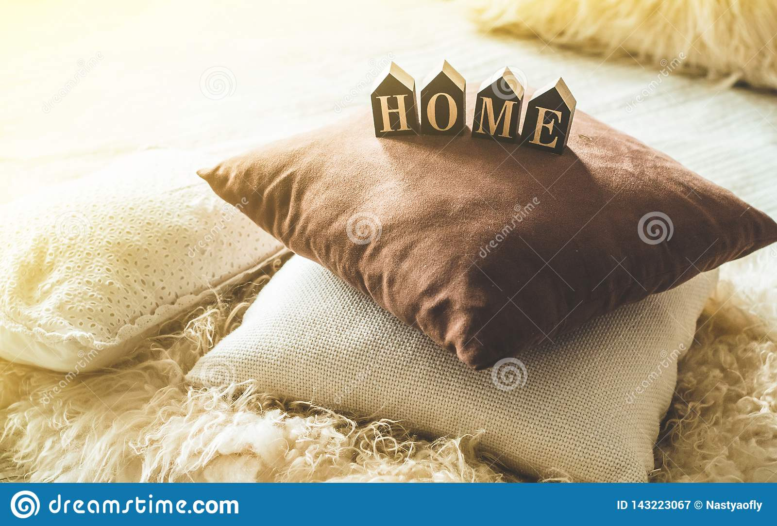 A lot of decorative cozy pillows and the inscription HOME