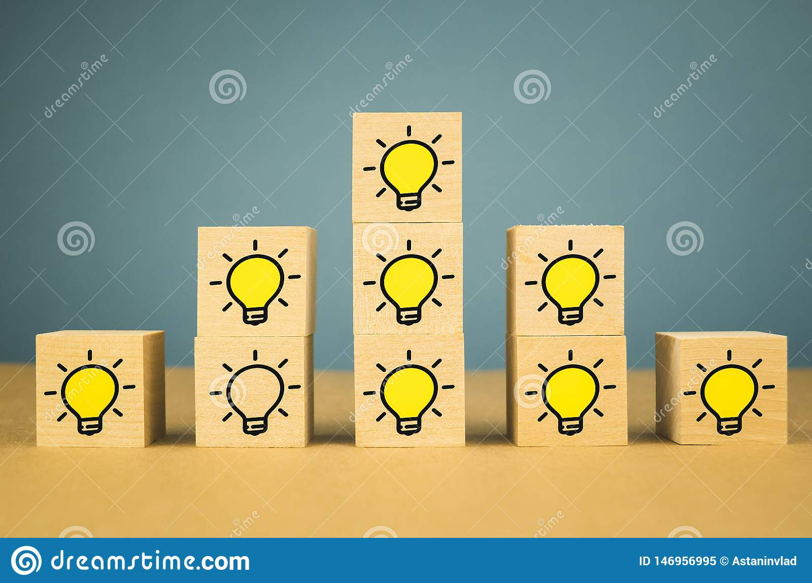 A lot of glowing light bulbs on wooden cubes and one light bulb is not burning, on a blue background