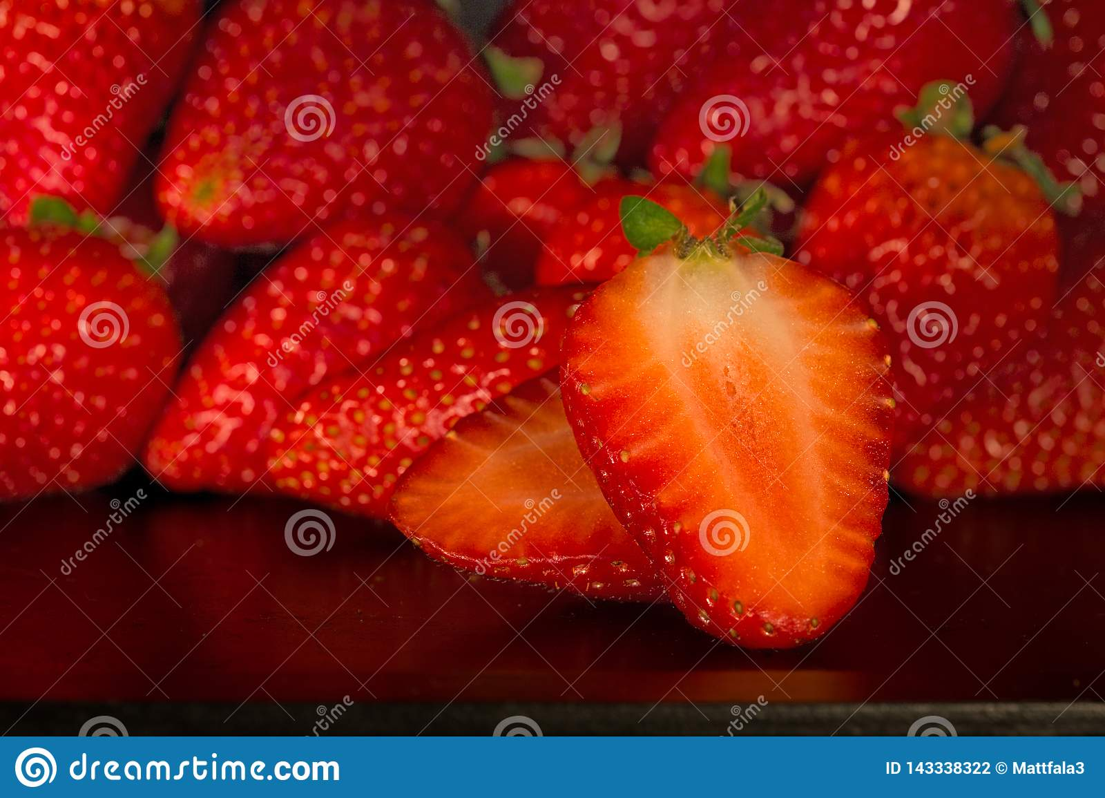 A lot of strawbarries on black tray