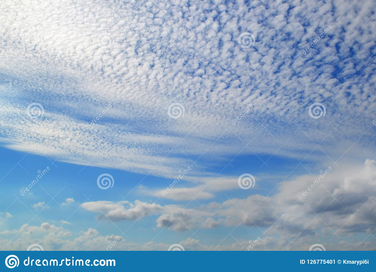 A lot of white clouds of different types: cumulus, cirrus, layered high in blue sky