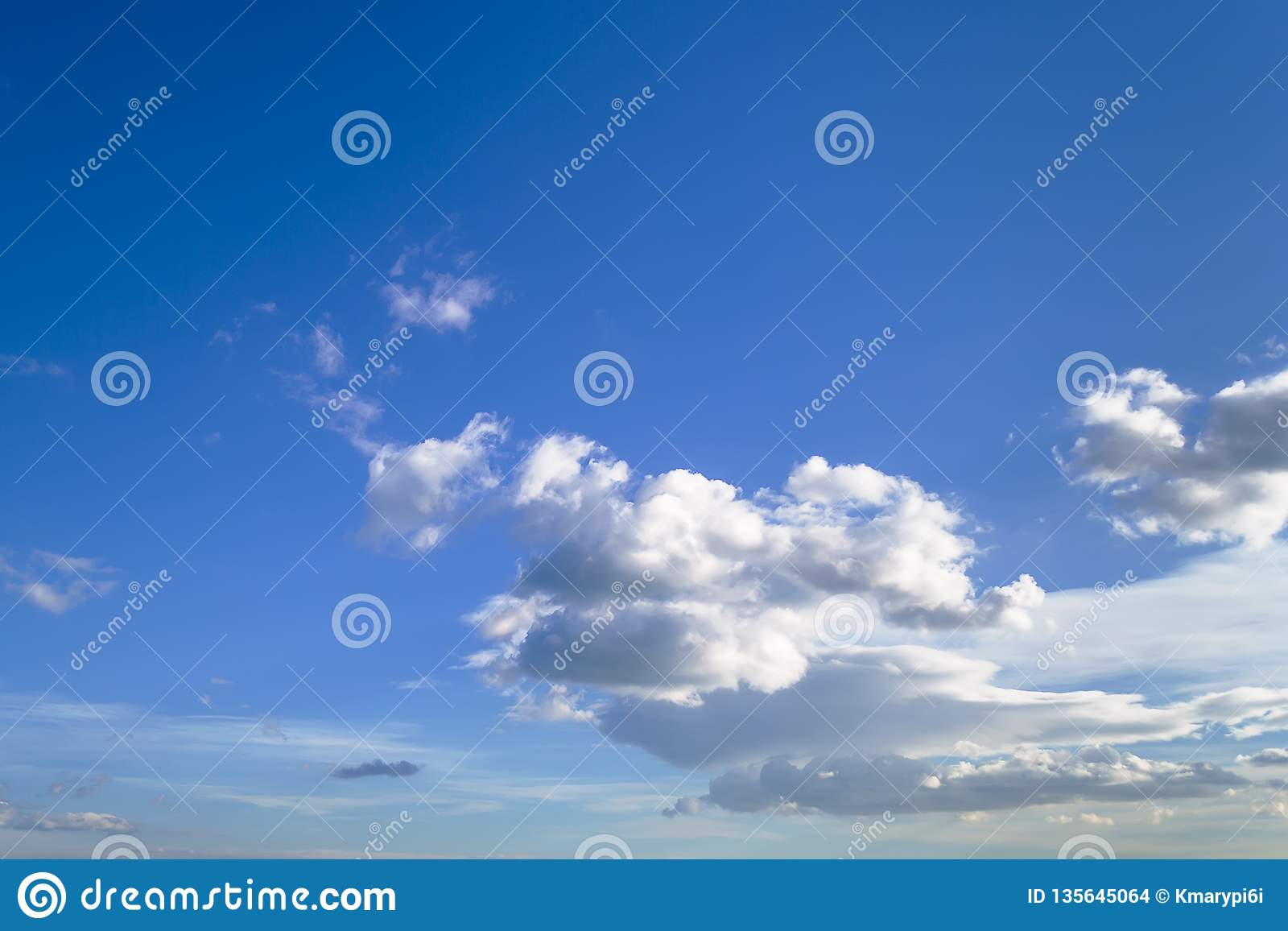 A lot of white scenic clouds high in blue sky on a sunny day, atmosphere skyscape