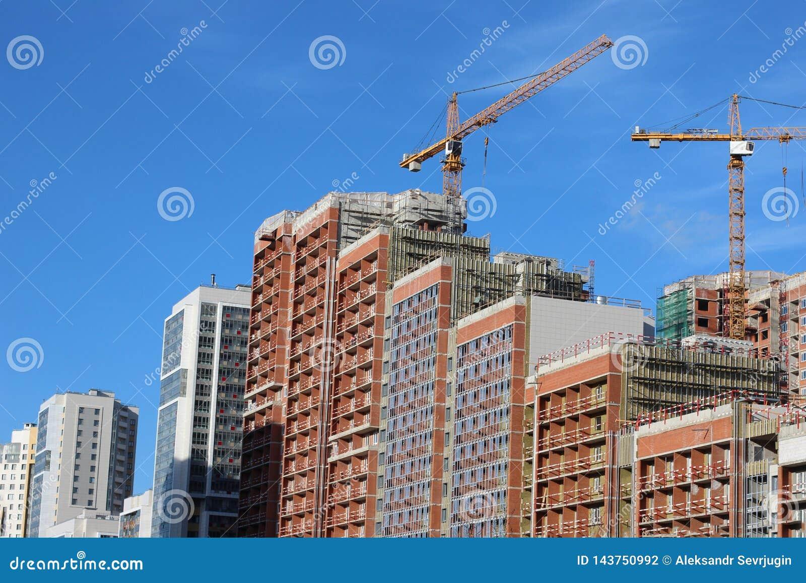 Lotes do canteiro de obras da torre com guindastes e da construção com fundo do céu azul