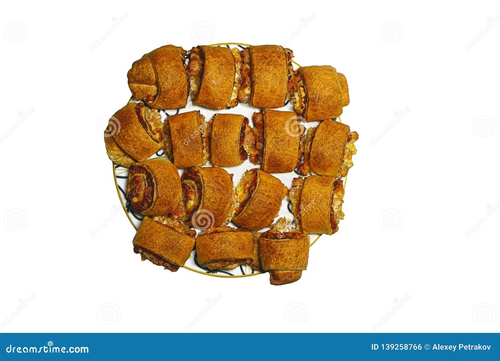 Five baked meat rolls on a platter