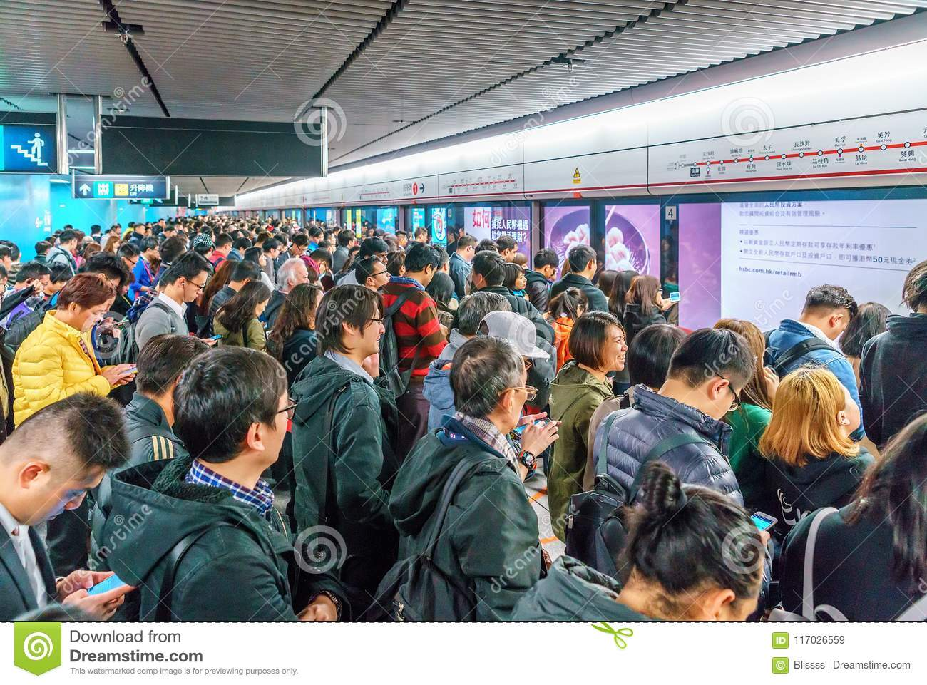 Lots of busy Chinese people crowding at subway station in Central District of Hong Kong waiting for a train to arrive