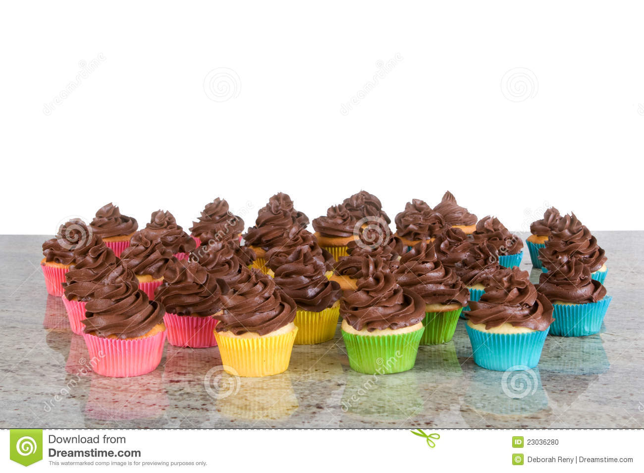 Lots of chocolate frosted cupcakes in rainbow wrappers - isolated on ...