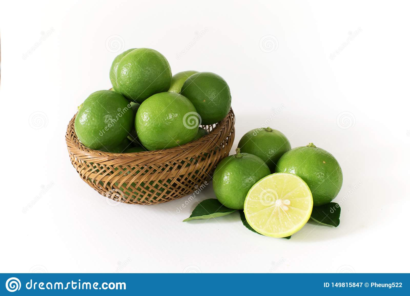 Lots of green lemon are in a wooden basket. And some of the outside with lemon slices cut in half on the side