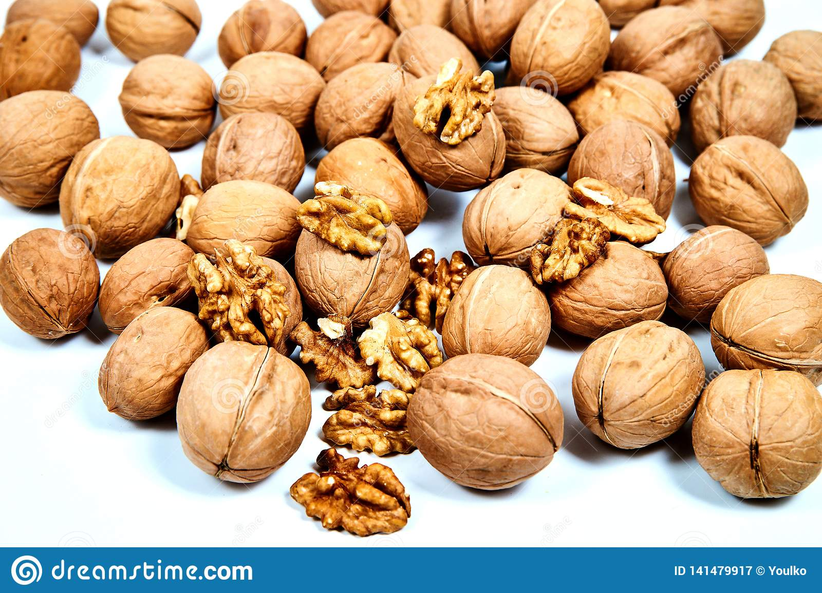 Lots of inshell Walnuts on white background