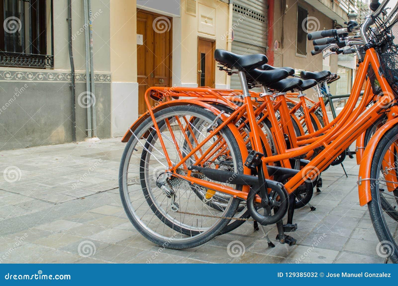 Louer le vélo orange sur la rue à Valence