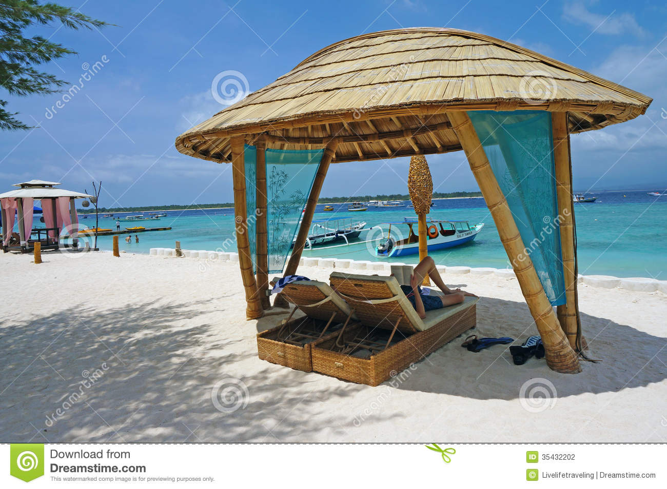 Lounge Chairs Shaded By A Bamboo Hut On The Beach Stock