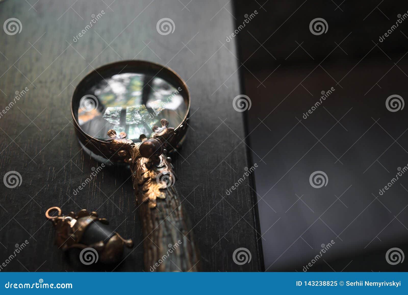 Loupeclose-up, uitstekende meer magnifier met de hand gemaakt op donkere houten lijstachtergrond, concept onderzoek, onderzoek, p