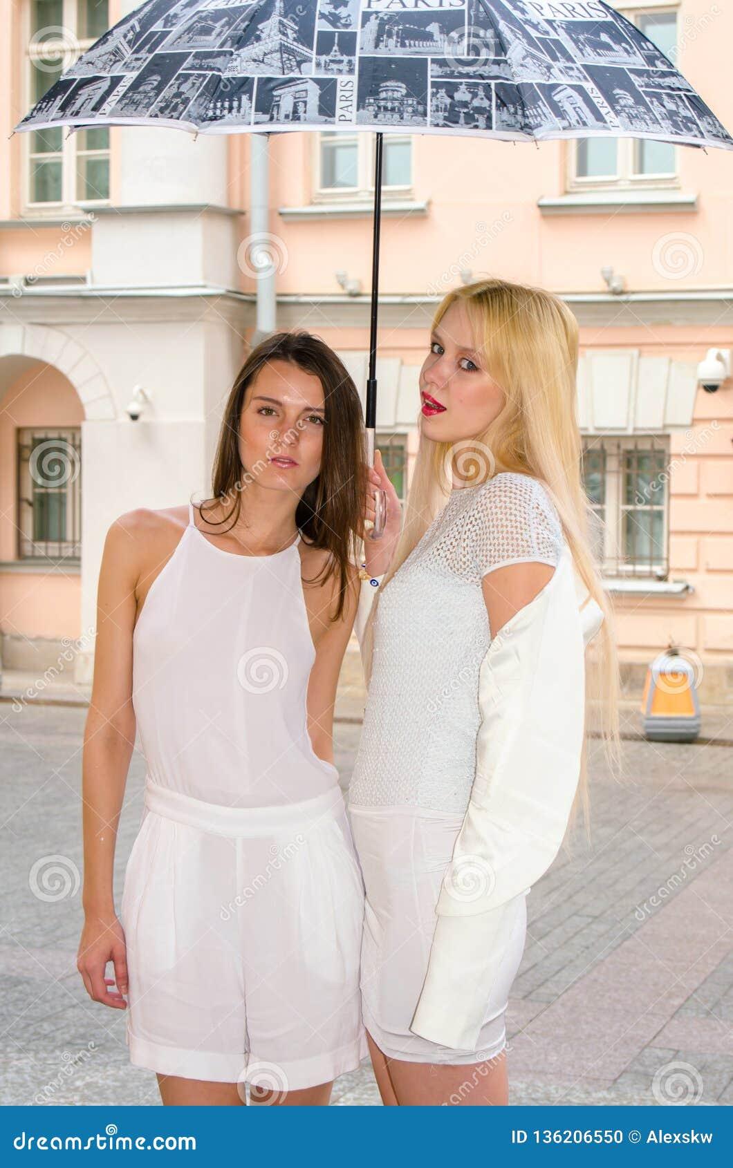 Louro de dois amigos e moreno nos vestidos brancos que escondem do tempo sob um grande guarda-chuva nas aleias da cidade velha