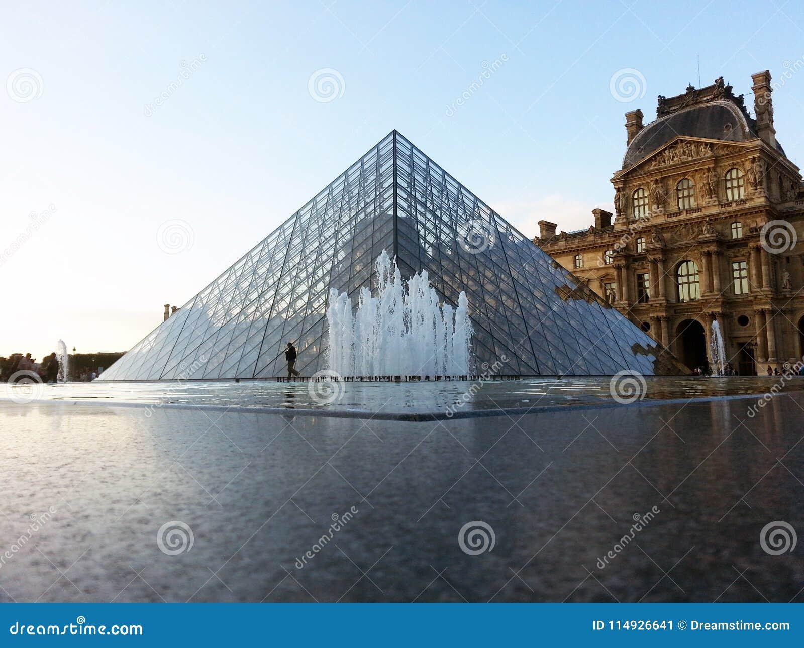 Louvremuseumspringbrunn och pyramid