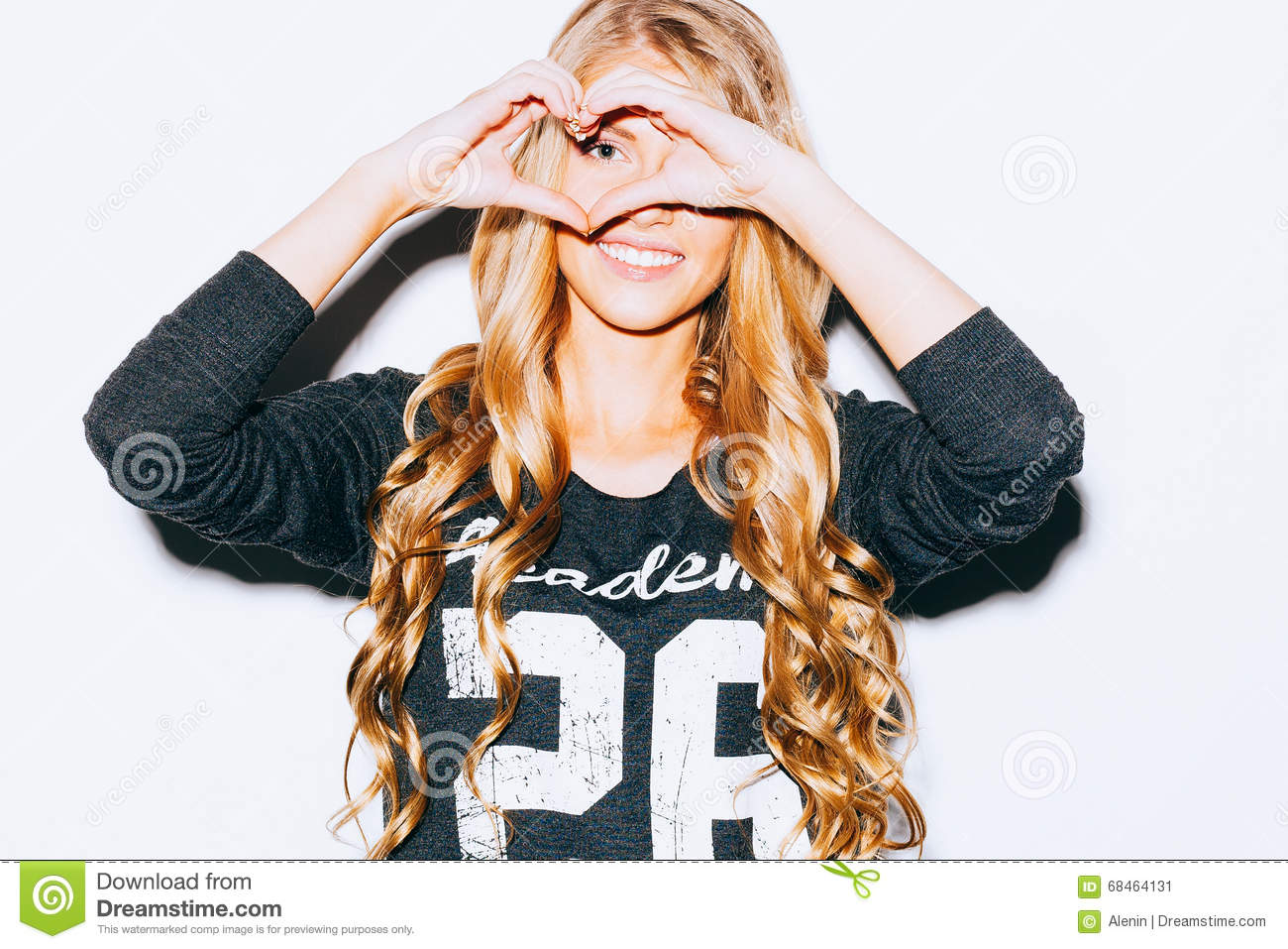 Love. Closeup portrait smiling happy young woman with long blon hair, making heart sign, symbol with hands white wall background.