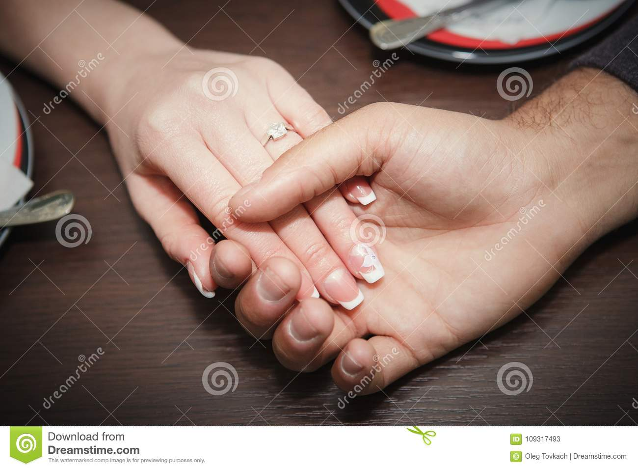 love concept -close up of engaged couple holding hands with diamond ring over holidays lights background