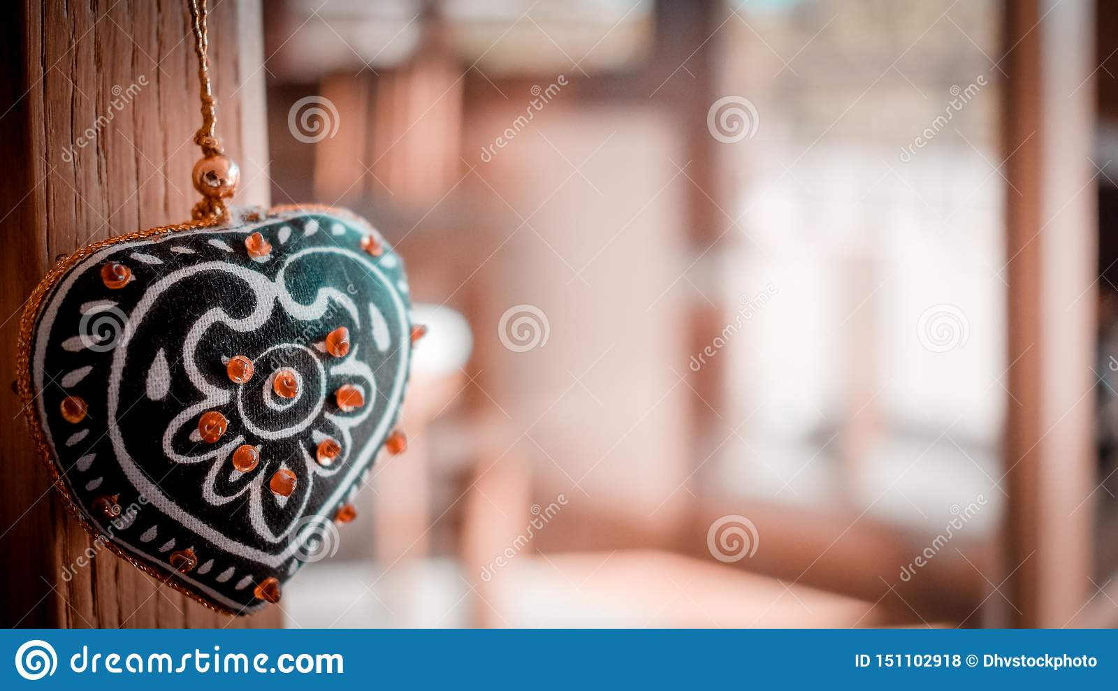 Love concept with decorative heart hanging and unfocused house background
