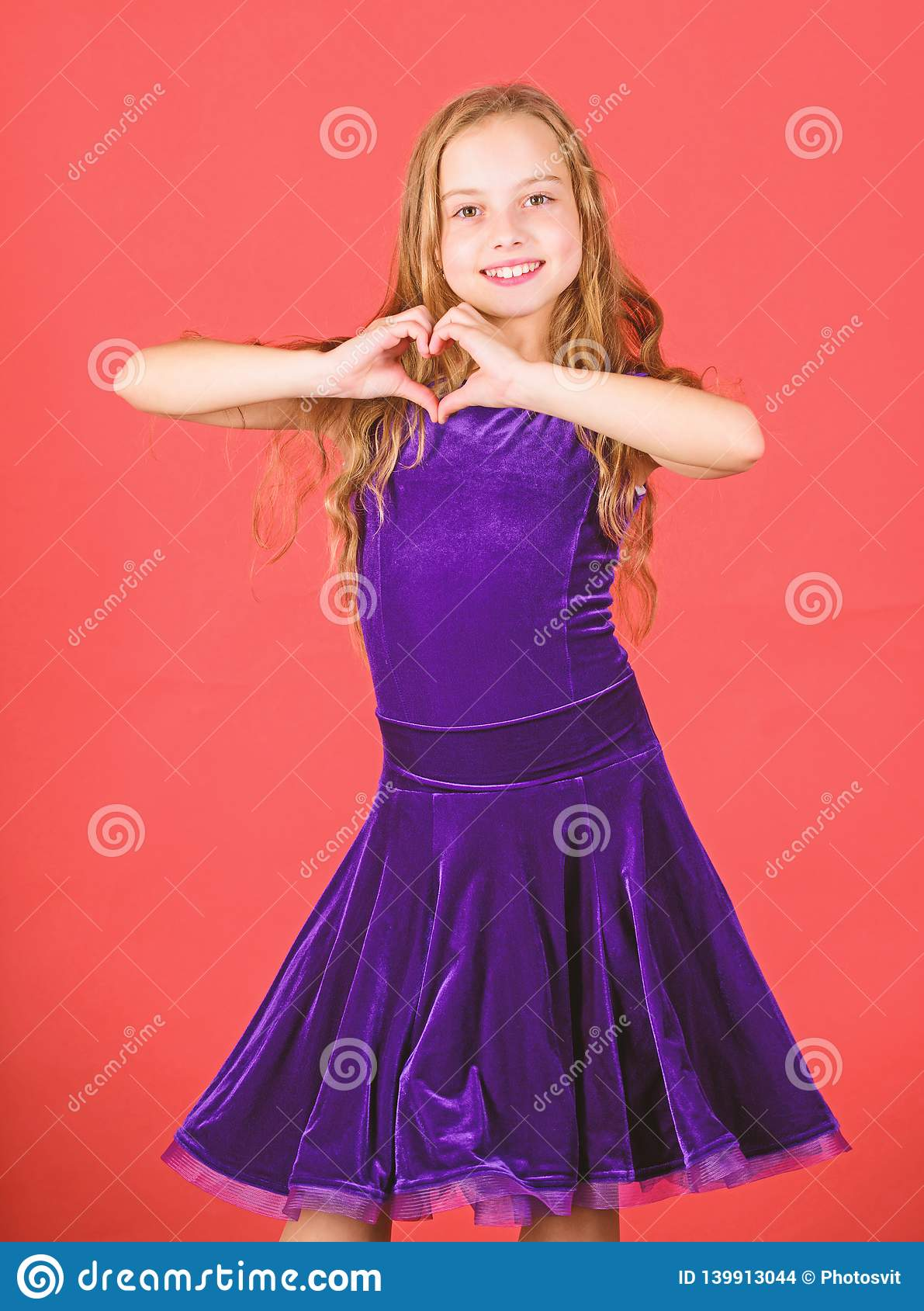 Love concept. Girl cute child show heart shaped hand gesture. Symbol of love. Kid adorable girl with long hair smiling