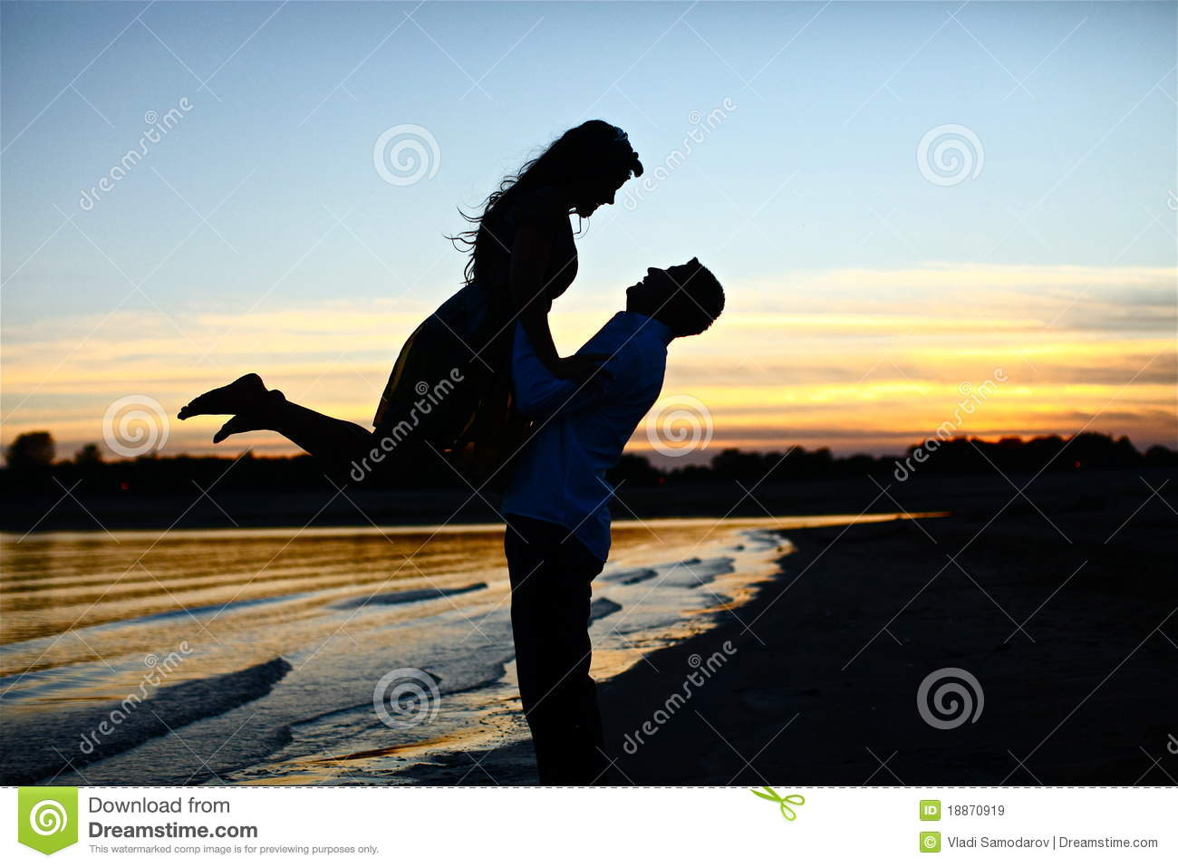 Silhouette of in love couple on beach with a beautiful sunset.