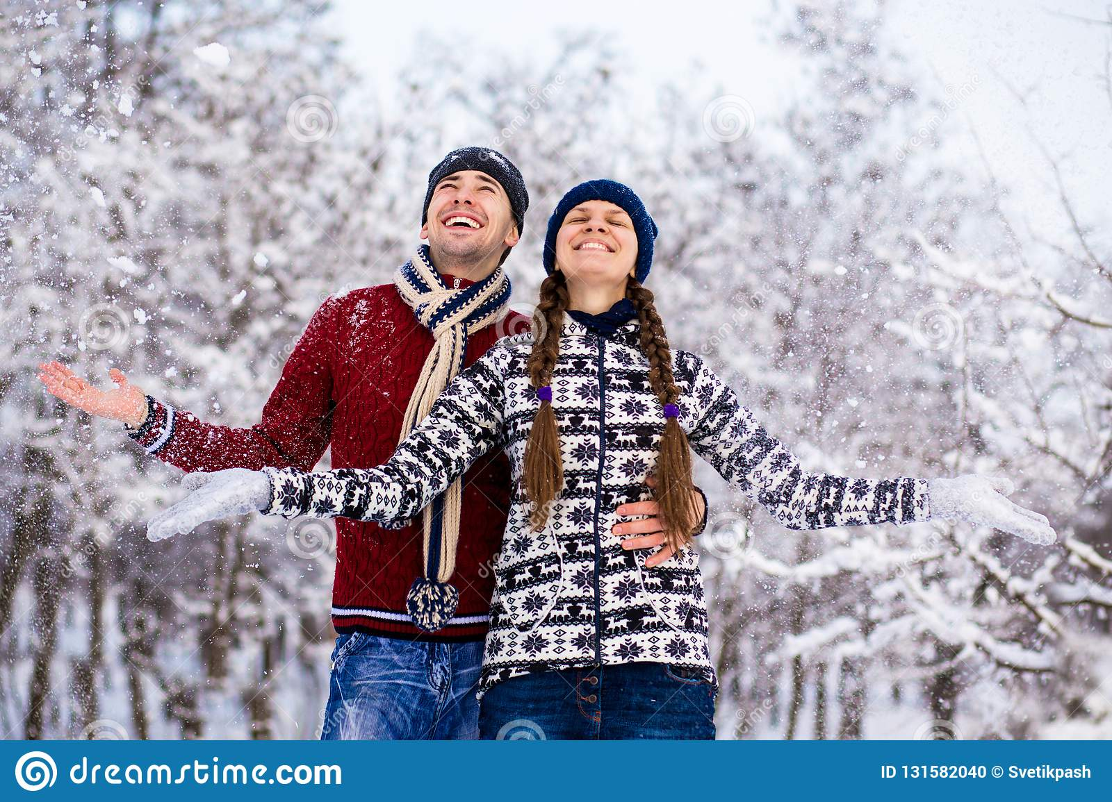 Love couple in bright clothes playing outdoors in winter