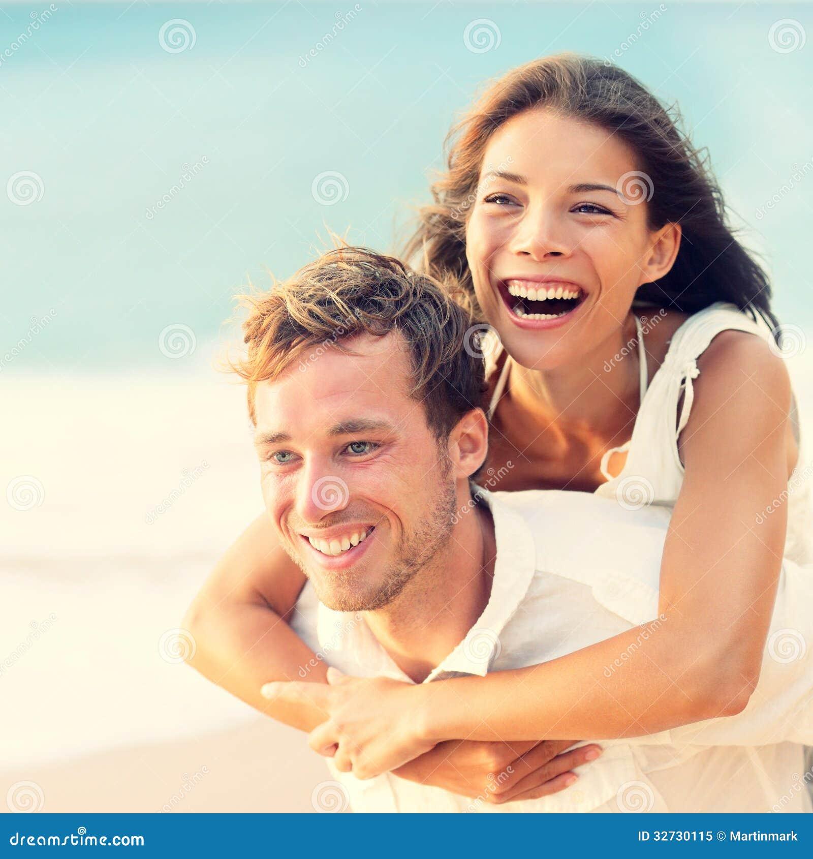 Happy Couple On Beach Having Fun Piggyback Stock