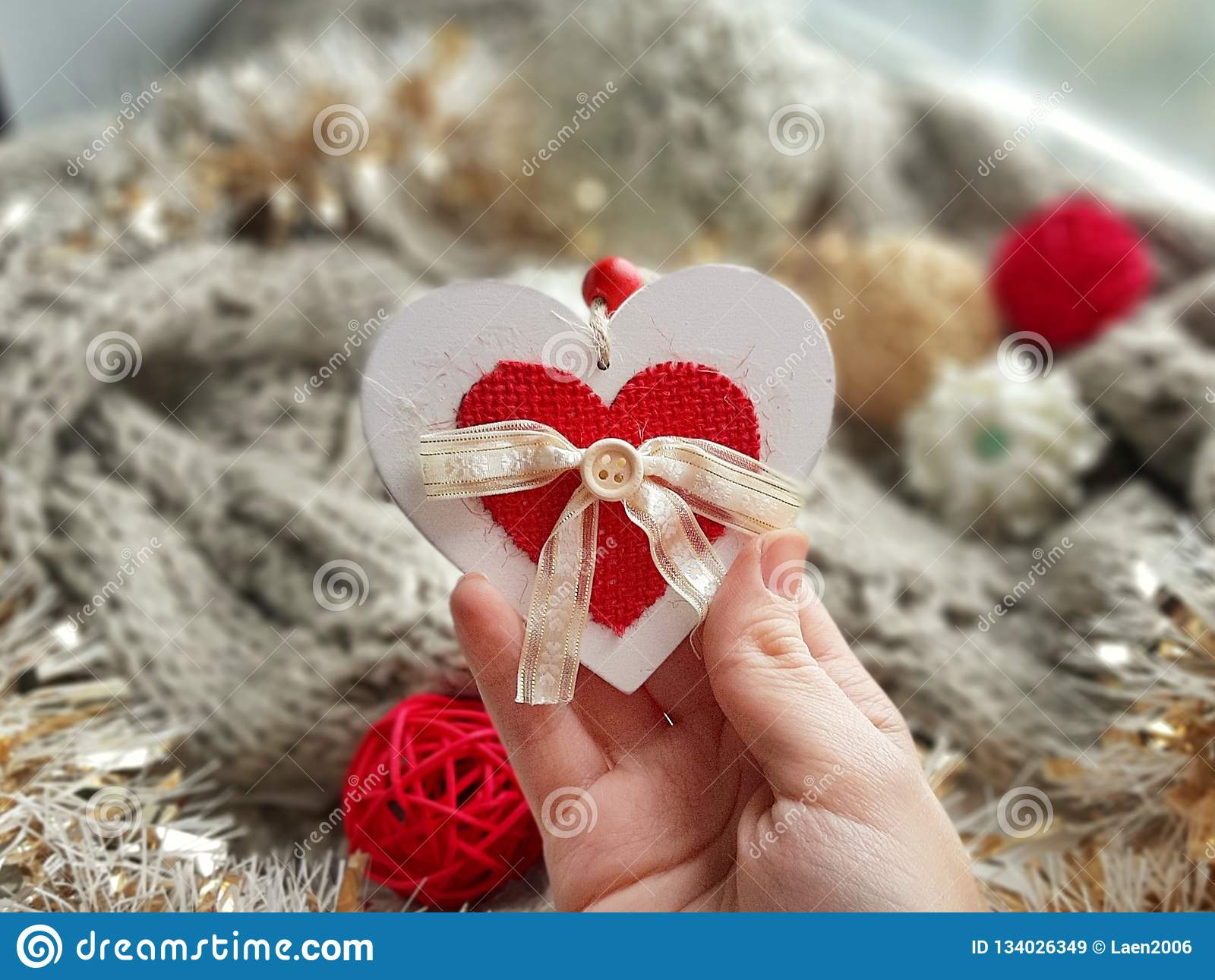 Love holiday greeting card. White and red heart in woman hand on cozy hygge background.